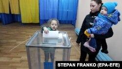 Дівчинка опускає у виборчу урну бюлетень своєї матері, Київ, 31 березня 2019 року