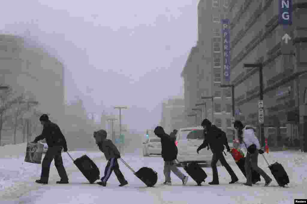 Travelers leave a train station in Boston, Massachusetts, where nearly two feet (60 centimeters) of snow fell in some areas.
