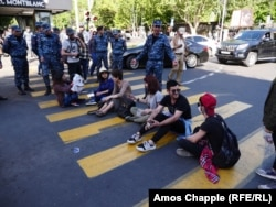 A driver and a policeman argue with students blocking an intersection in the center of Yerevan on April 25.