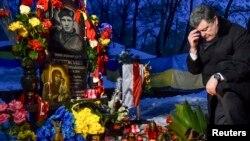 Петр Порошенко Киевте Еуромайдан толқуында қаза тапқандарға арналған ескерткішке гүл шоғын қойып, тағзым жасап тұр. Киев, 22 қаңтар 2015 жыл.