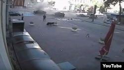 Адразу пасьля выбуху машыны Паўла Шарамета. Мужчына ў чорным з кійком зьлева - меркаваны забойца (паводле Анджэя Мрочка)
