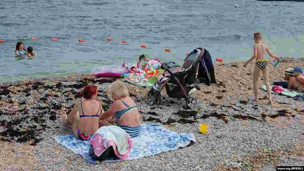 Батьки з дітьми засмагають на березі мілководної ділянки пляжу для дітей