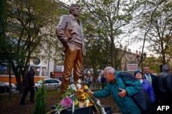 People lay flowers in front of a newly inaugurated statue of Markov in Sofia, Bulgaria, in November 2014.