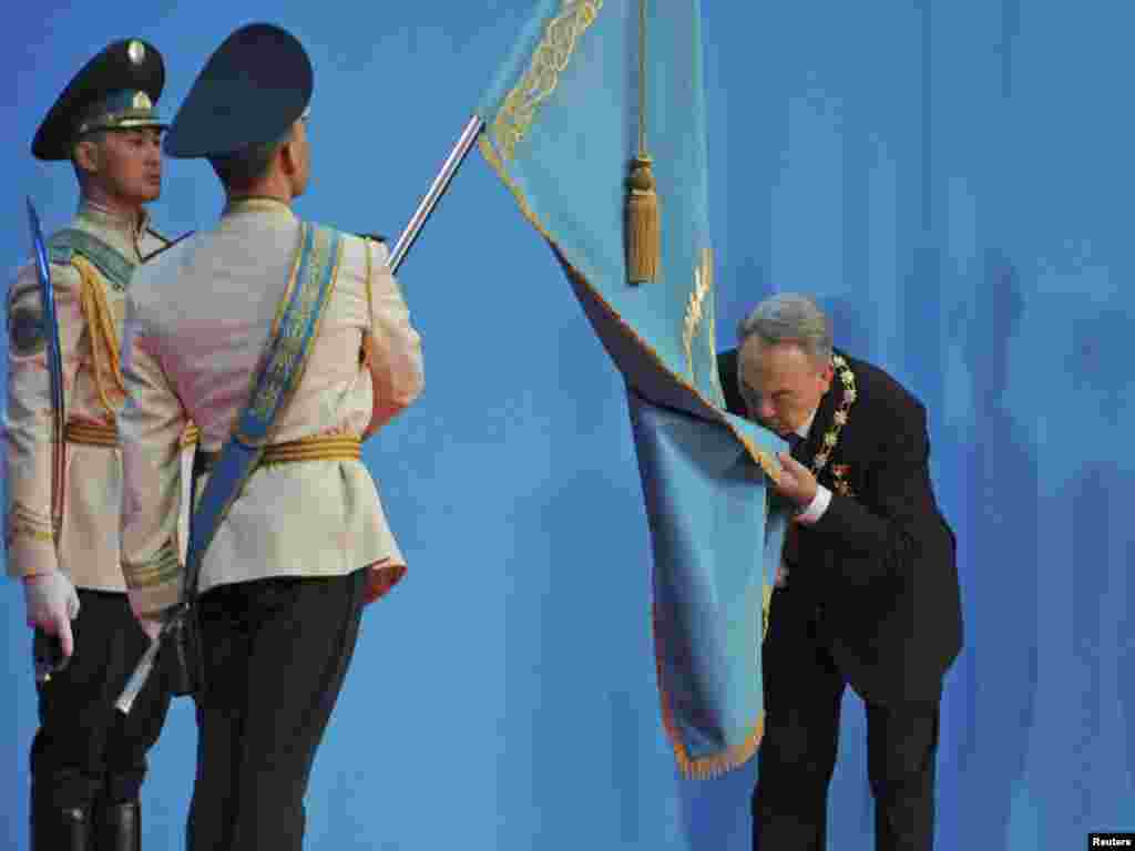 Kazakh President Nursultan Nazarbaev kisses the national flag during his inauguration in Astana on April 8. (Reuters/Mukhtar Kholdorbekov)