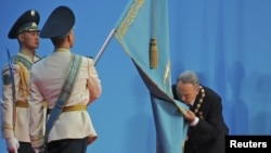 No kiss goodbye: Kazakh President Nursultan Nazarbaev kisses the national flag during his inauguration ceremony for a fourth term in Astana on April 8.