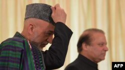 Visiting Afghan President Hamid Karzai (left) is flanked by Pakistani Prime Minister Nawaz Sharif as he adjusts his cap in Islamabad on August 26.