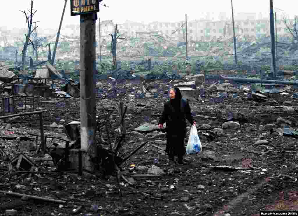 A woman picks her way through the rubble in Grozny. After being targeted twice in less than a decade, Chechnya's capital was the most destroyed city on earth.