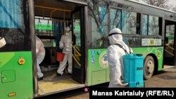 Жұмысшылар Алматыдағы автобустарды дезинфекциялап жатыр. 18 наурыз 2020 жыл.