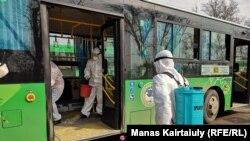 Работники в защитных костюмах на дезинфекции общественного транспорта. Алматы, 18 марта 2020 года.