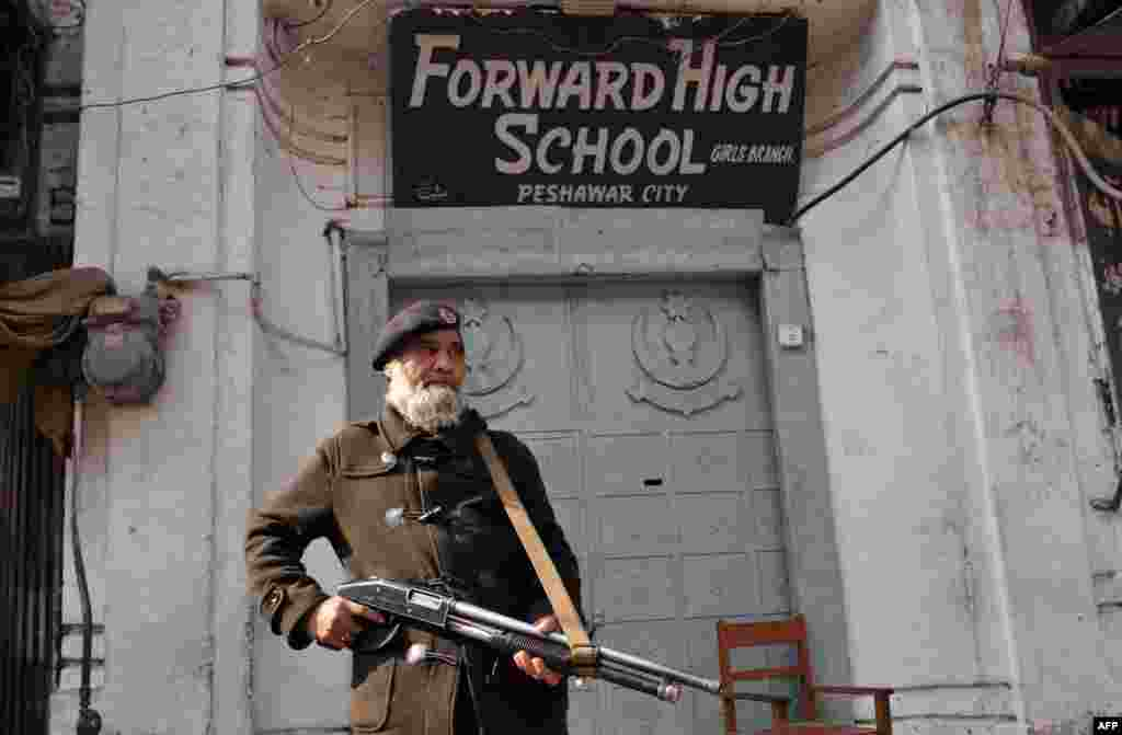 A policeman stands guard in front of a school soon after a militant attack killed more than 20 students and teachers at Bacha Khan University on January 20.