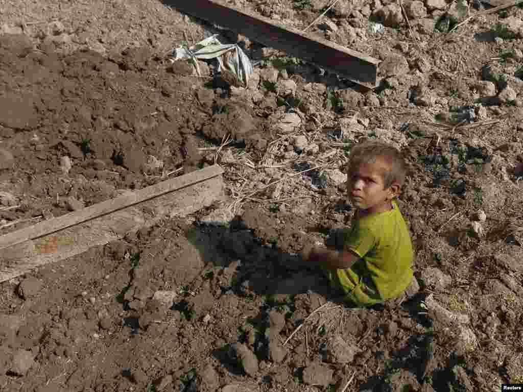 Дворічний хлопчик сидить біля руїн власного будинку, зруйнованого повінню, селище приблизно в 320 кілометрах на Північ від Карачі, 24 вересня.Photo by Akhtar Soomro for Reuters