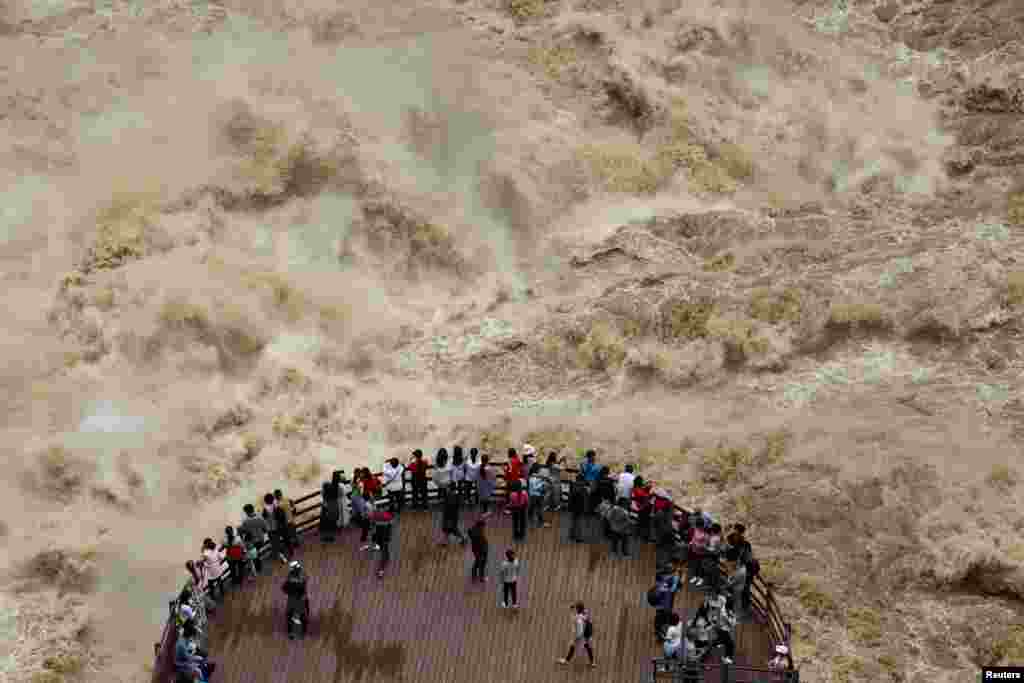 People watch the flooded Jinsha River from a sightseeing platform in the Tiger Leaping Gorge in China's Yunnan Province on July 15. (Reuters)