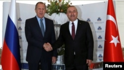 Russian Foreign Minister Sergei Lavrov (left) shakes hands with Turkish counterpart Mevlut Cavusoglu in Alanya, Turkey, on December 1.