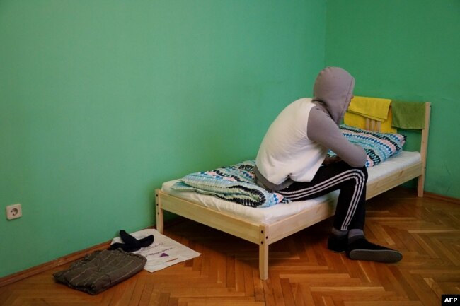 A Chechen man who fled the republic due to his sexual orientation sits on his bed in Moscow on April 17.