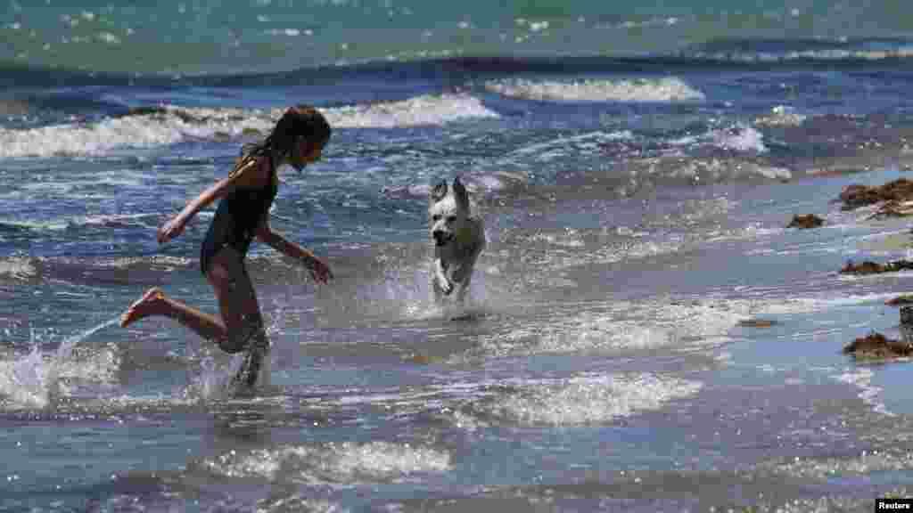 Девочка бегает со своей собакой вдоль линии пляжа в Евпатории