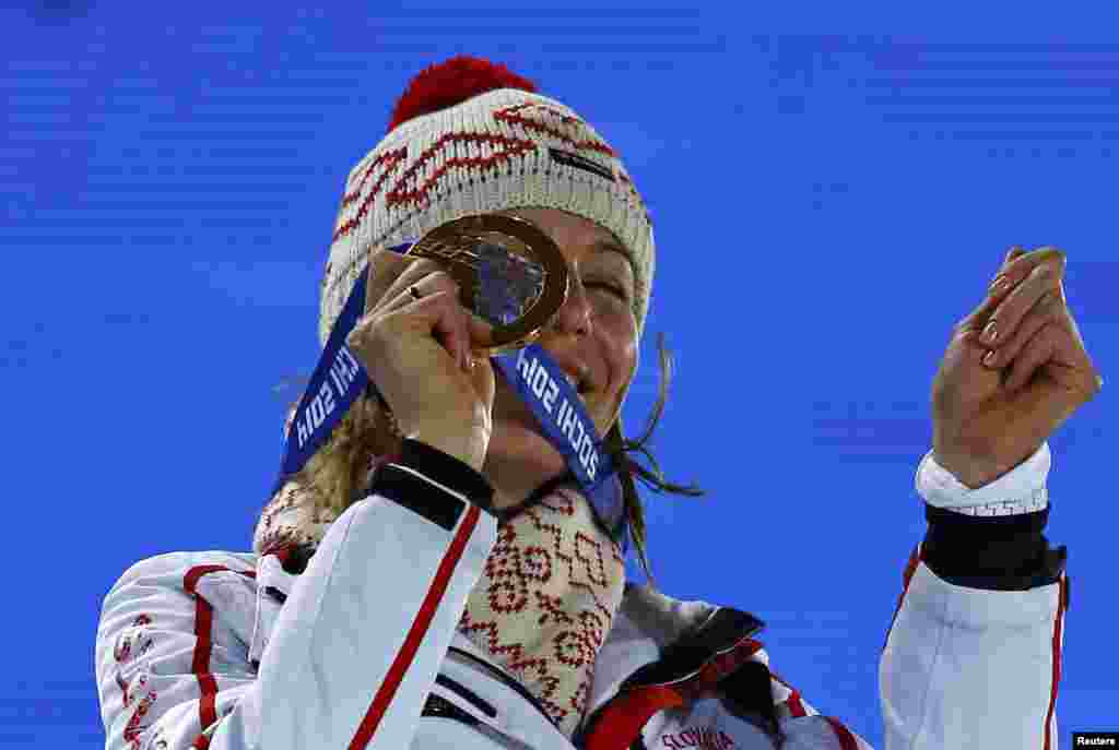 Gold medalist Anastasia Kuzmina of Slovakia smiles as she holds up her medal, during the medal ceremony for the women's biathlon 7.5-kilometer sprint event.