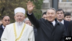 Kazakh President Nursultan Nazarbaev waves next to Absattar Derbisali, the supreme mufti of Kazakhstan, as he visits the Central Mosque in Almaty in November 2010.