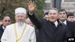 Kazakh President Nursultan Nazarbaev waves next to Absattar Derbisali, the supreme mufti of Kazakhstan, as he visits the Central Mosque in Almaty in November 2010.