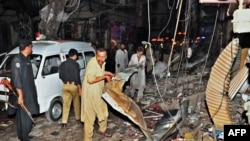 Would-be rescuers and police at the scene of the twin bombings that killed dozens at a crowded market in Peshawar on June 11 and 12