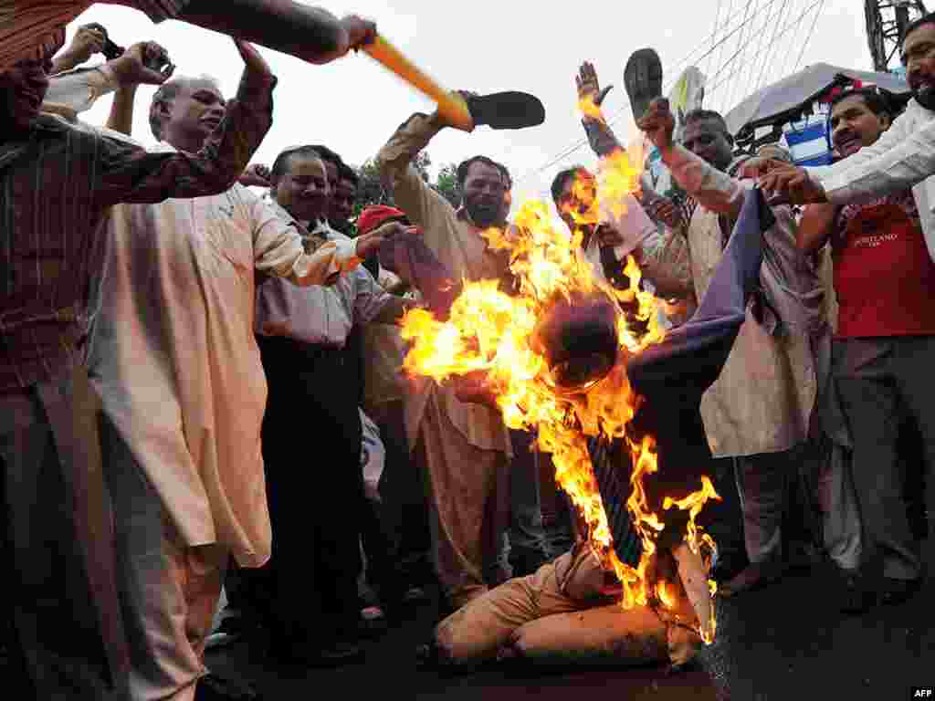Pakistani Christians beat a burning effigy of Dove World Outreach Center Pastor Terry Jones during a protest in Lahore on September 9, held to denounce Jones' plans, since suspended, to burn copies of the Koran. Photo by Arif Ali for AFP