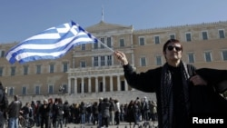 A woman waves a Greek flag during an anti-austerity rally in front of the parliament in Athens on February 19.