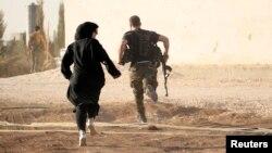 Атыс кезінде жүгіріп бара жатқан әйел. Алеппо. Сирия. (Көрнекі сурет).