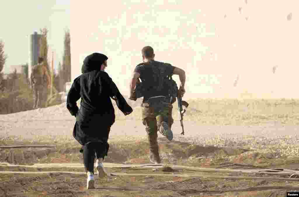 A woman reporter runs with a rebel fighter to avoid snipers at the frontline against Islamic State jihadists in northern Syria on October 10. (Reuters/Jalal Al-Mamo)