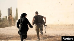 A female reporter runs with a rebel fighter to avoid snipers on the front line against Islamic State fighters in Aleppo's northern countryside in October.