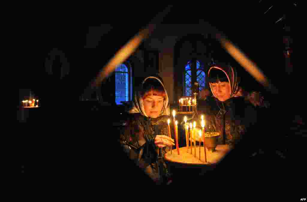 Two sisters light candles during an Orthodox Christmas service in a church in the Kyrgyz village of Sokuluk, near the capital, Bishkek. (AFP/Vyacheslav Oseledko)