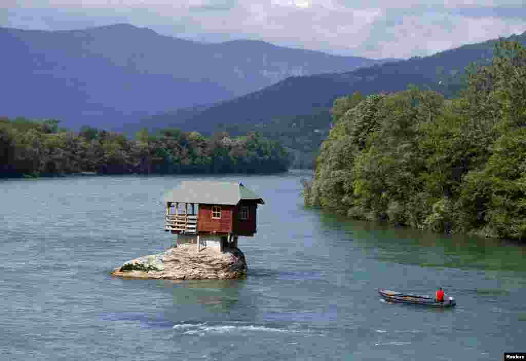 A man on a boat passes a house built on a rock on the Drina River near the western Serbian town of Bajina Basta. The house was built in 1968 by a group of young men who decided that the rock was an ideal place for a tiny shelter. (Reuters/Marko Djurica)