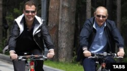 President Dmitry Medvedev and Prime Minister Vladimir Putin ride bicycles during an informal meeting at the Gorki residence outside Moscowon June 11.