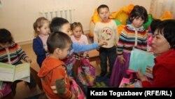 Дети рассматривают полученные в мини-центре подарки. Алматы, 14 февраля 2013 года.