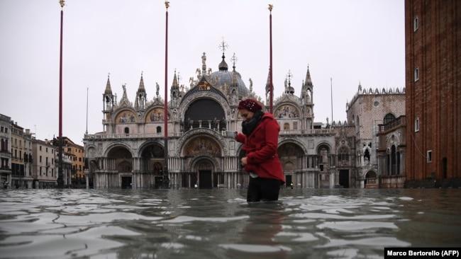 Një grua ecë pranë bazilikës së Shën Markut në Venecia.