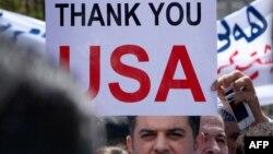 Иракский христианин поднимает плакат с благодарностью в адрес США на демонстрации у американского консульства в Ириби (один из центров населенной курдами области). Август 2014 года.