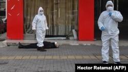Вирус шыққан Ухань қаласында санитар мамандар қаза тапқан адамның жанында тұр. 30 қаңтар 2020 жыл.