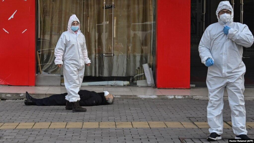 Медработники в защитных костюмах эвакуируют умершего на улице в Ухане рядом с одной из местных больниц, 30 января 2020 года<br />