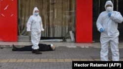 Медработники в защитных костюмах эвакуируют умершего на улице в Ухане рядом с одной из местных больниц, 30 января 2020 года.