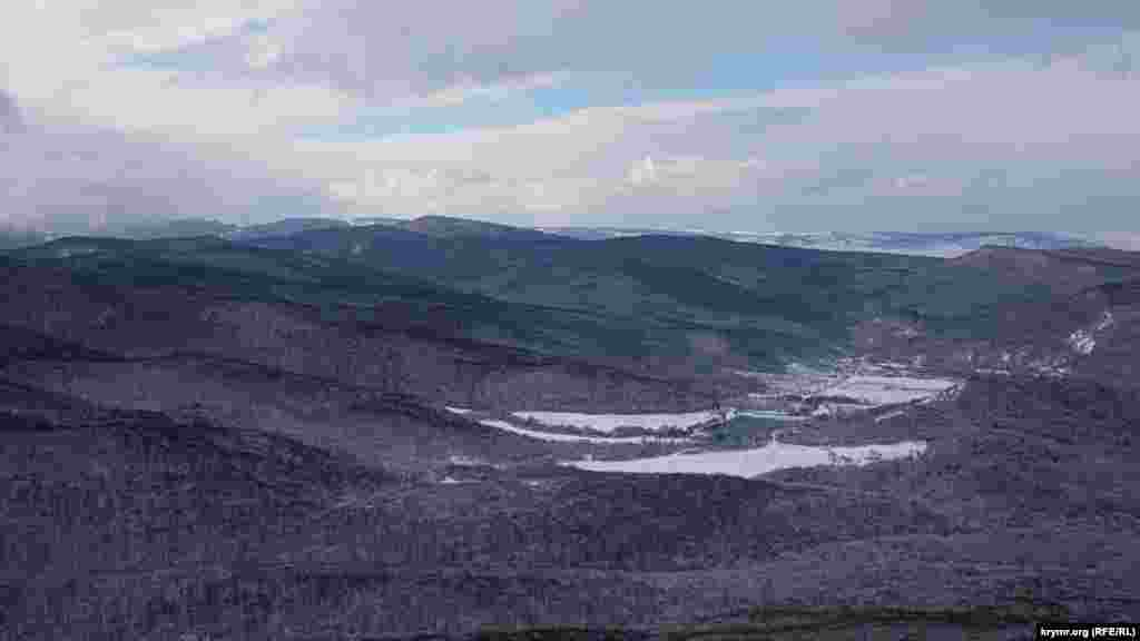 Qayanıñ töpesinden Belbek özeniniñ uvasına manzara açıla, yaqınlarda Hmelev suv anbarıdır
