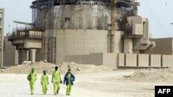Иранские рабочие на фоне АЭС в Бушере - городе в 1300 километрах к югу от Тегерана.