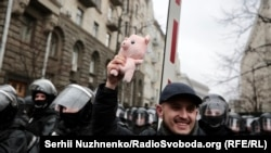 A protester with a toy pig in Kyiv