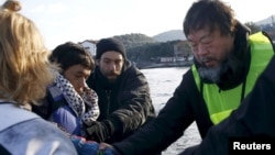 Chinese artist Ai Weiwei (R) helps an Afghan migrant as he arrives with other refugees and migrants on a raft on the Greek island of Lesbos on January 25.