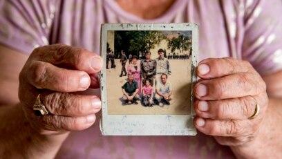 Hasiba Zlatarac drži fotografiju na kojoj su suprug Huso (lijevo u prvom redu), sin Nedžad (u centru u drugom redu) i brat Fikret (desno u prvom redu)