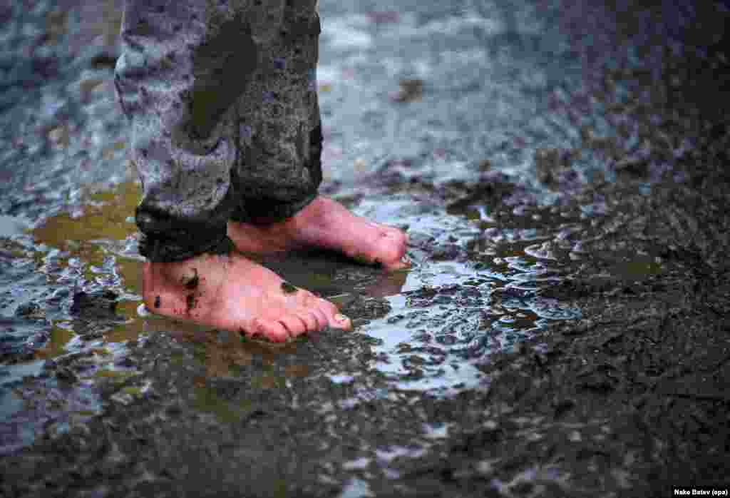 A migrant  boy stands barefoot in the mud at a refugee camp on the border between Greece and Macedonia on March 16. (epa/Nake Batev)