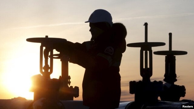 A worker checks the valve of an oil pipe at the LUKoil company-owned Imilorskoye oil field outside the western Siberian city of Kogalym.