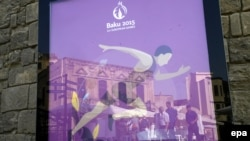 Azerbaijan -- People are reflected in a poster promoting the Baku 2015 European Games in Baku, June 11, 2015