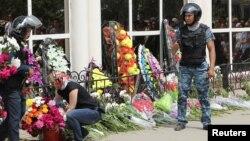 Женщина возлагает цветы у оружейного магазина в день похорон погибшего от рук предполагаемых исламистов продавца Андрея Максименко. Актобе, 8 июня 2016 года.