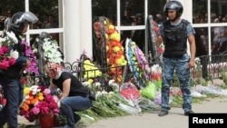 A woman places flowers as Interior Ministry troops stand guard outside a gun shop that was attacked during the funeral of salesman Andrei Maksimenko in Aqtobe on June 8.