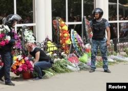 Вооруженная охрана у цветов, которые люди принесли к зданию оружейного магазина — месту гибели первых жертв событий 5 июня. Актобе, 8 июня 2016 года.