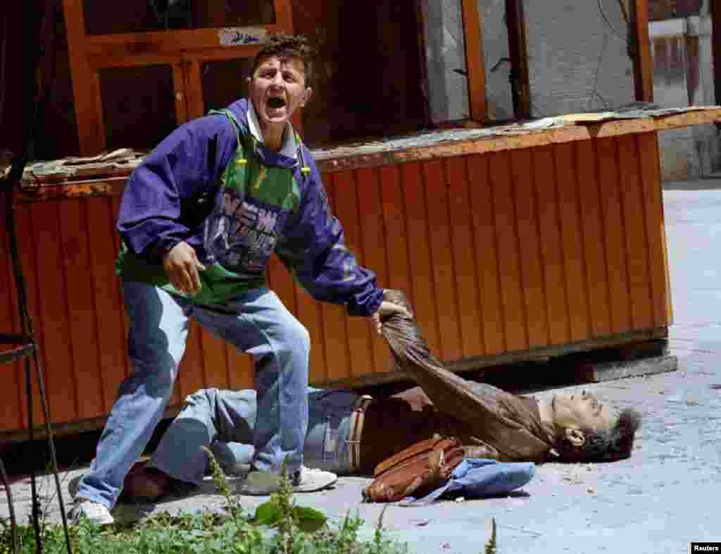 Мужчина зовет на помощь раненному при обстреле.