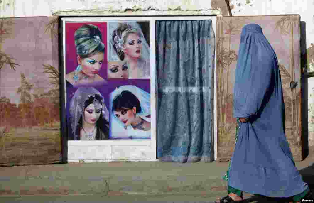 A woman in a burqa walks past a beauty salon in Kabul. (Reuters/Mohammad Ismail)